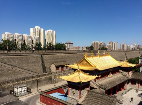 Xi'an is a city of contrasts, between its historical heritage and fast growing economy. Here we see an old temple within the city wall, with new apartment buildings as background