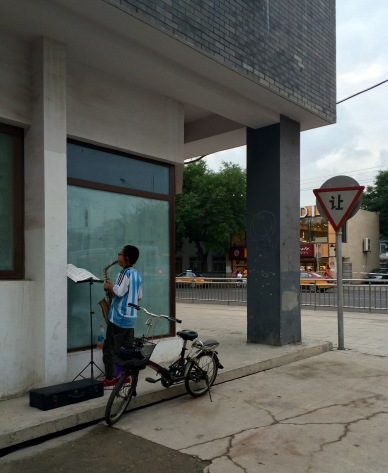 A kid practices saxophone on Beijing's streets