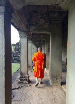 A Buddhist monk walking the aisles of Angkor Wat