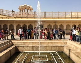 A happy group of Indian tourists enjoys the water show at Hawa Mahal