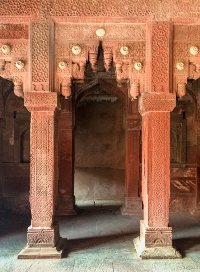 Delicate red sandstone carvings inside the Jahangiri Mahal