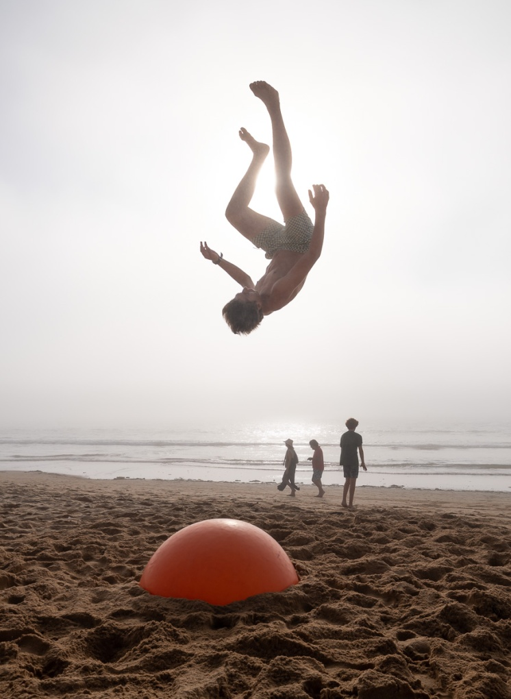 Acrobatic flip using an exercise ball buried in the sand, Praia América, Galicia, Spain (PPL1-Corrected)
